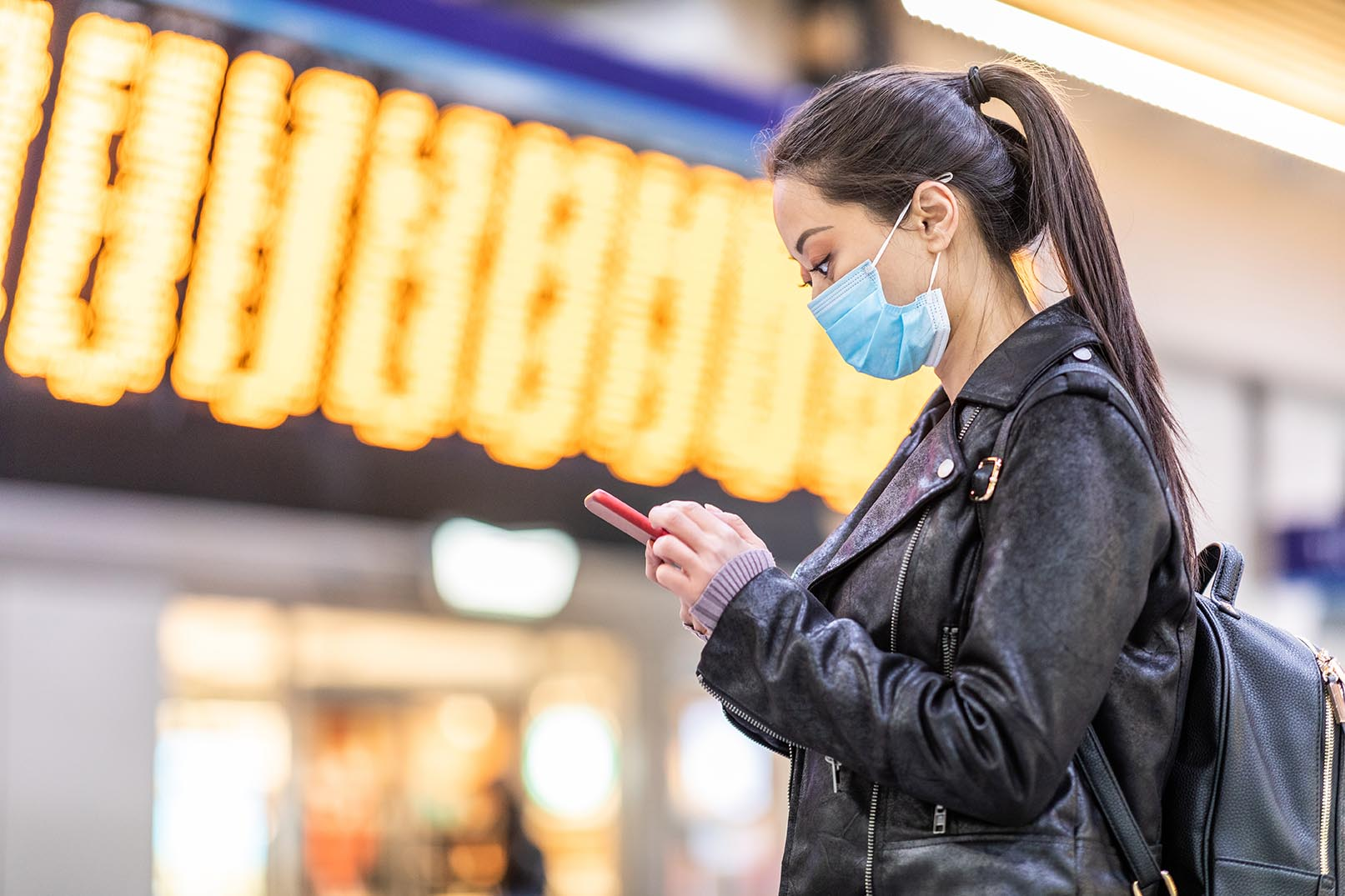 Woman with mask at rail station with departure board in background